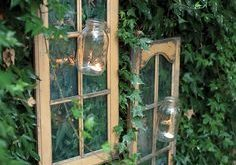 Old hutch doors removed and hung on the fence. Add a mason jar and tea light fo...