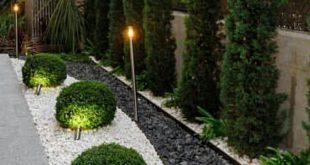 Sommerlicher Garten im Freien mit schwarzen und weißen Steinen, die in ein Gart...